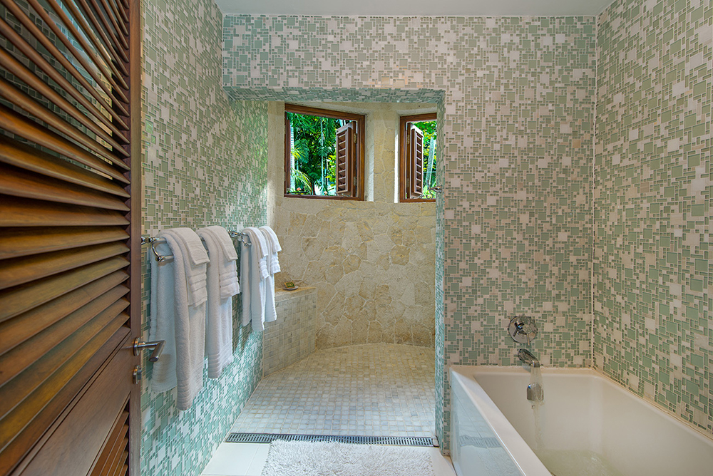 ... has an artistically curved walk-in shower and separate bathtub.