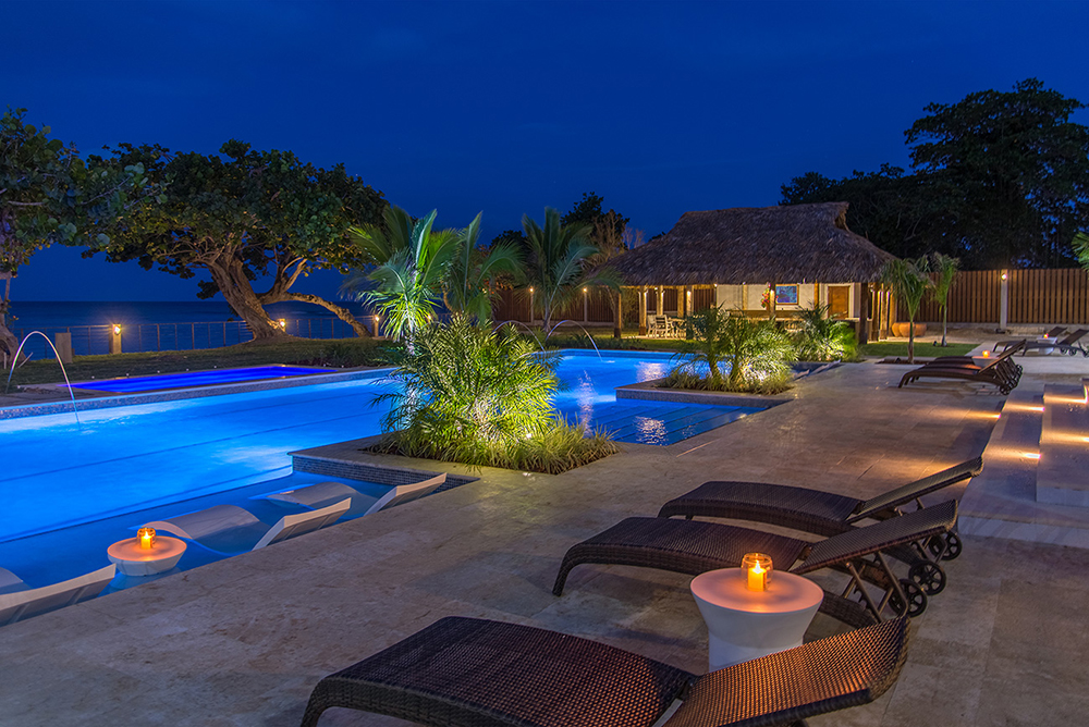 Fountains of rainbow colors provide a light show over the pool. Candles and treetops glow in the evening scene.