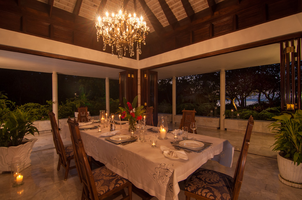 ... to a more formal dining room under a crystal chandelier.  Three window walls open wide to a view of the lit orchid tree and garden.