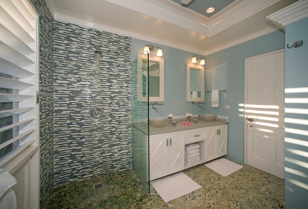 The shower features a clear glass partition and a mosaic of glass tiles ...