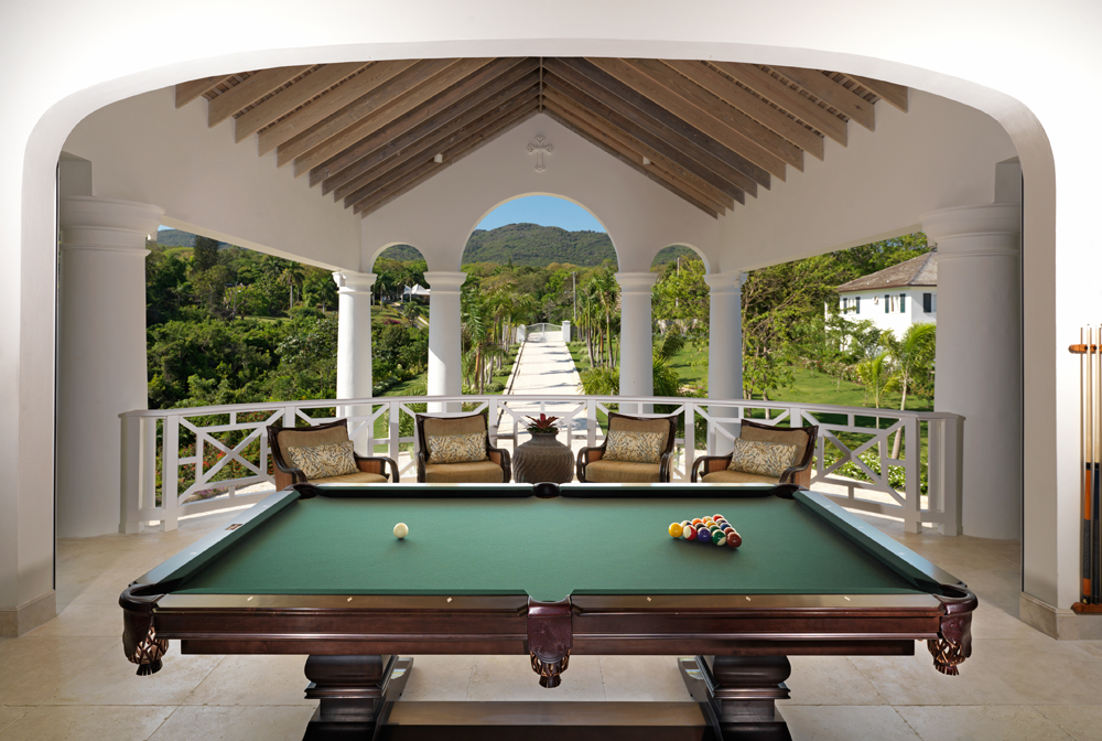 Beyond the TV sitting area is a favorite of all generations: the classic pool table with a view of the peak of the eponymous Flower Hill for which the home is named.