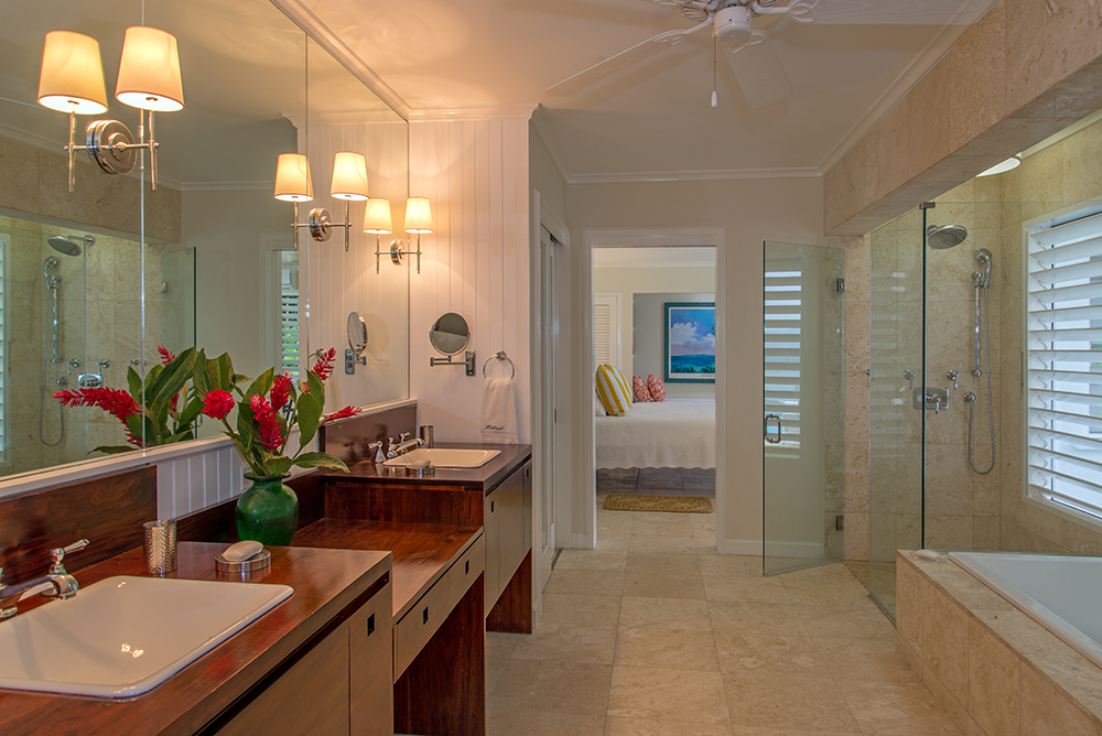 Notable in both downstairs  accommodations are identical glamorous bathrooms ... each with double vanity in custom mahogany cabinets, deep bathtub and glass-enclosed shower.  This pair of bed
