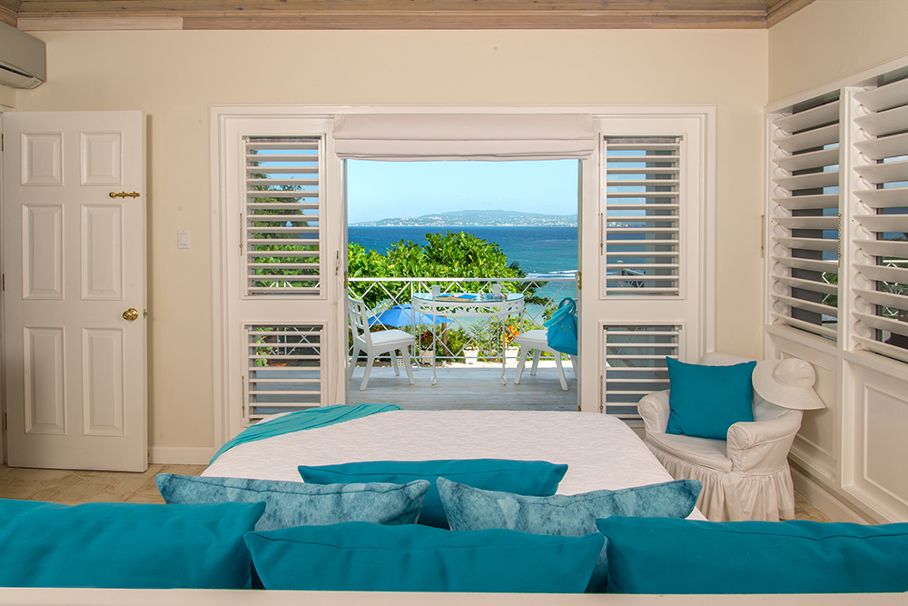 ACCOMMODATIONS UPSTAIRS Next to the living room is Bedroom 1.  Its queen bed faces a driftwood balcony and the incredible long blue view.