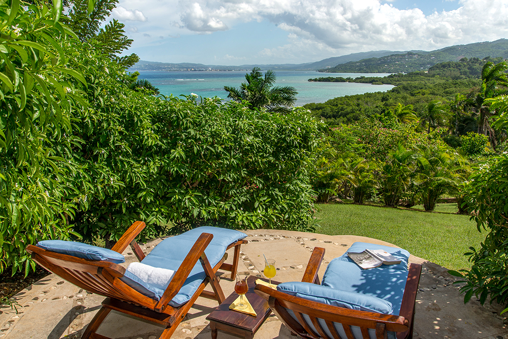 A few steps beyond the end of the pool is an intimate landscaped lounging deck with his 'n' hers deck chairs and a long view down the lush lawn.