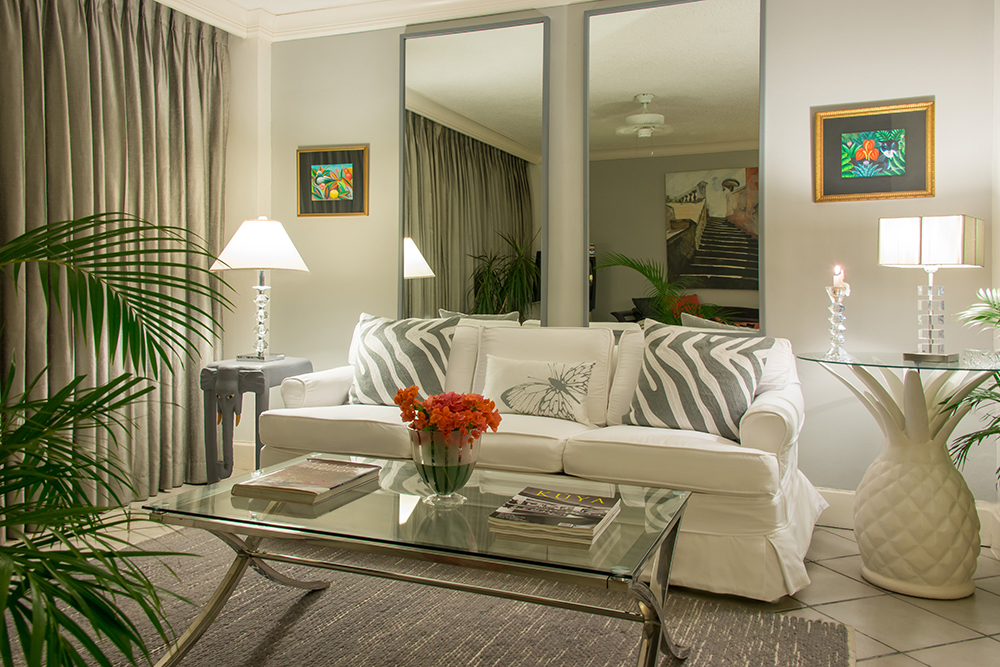 Interiors are smartly furnished.  Downstairs, the chic living area has soft gray walls, crisp white fabric and tall mirrors that bring the remarkable views into every corner. The queensize so