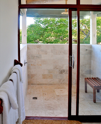 Bathrooms here merit mention.  The cantilevered treehouse-style shower has a front row view of the sea, sky and stars ... and plumbing hidden from view in a large overhead hollow log.