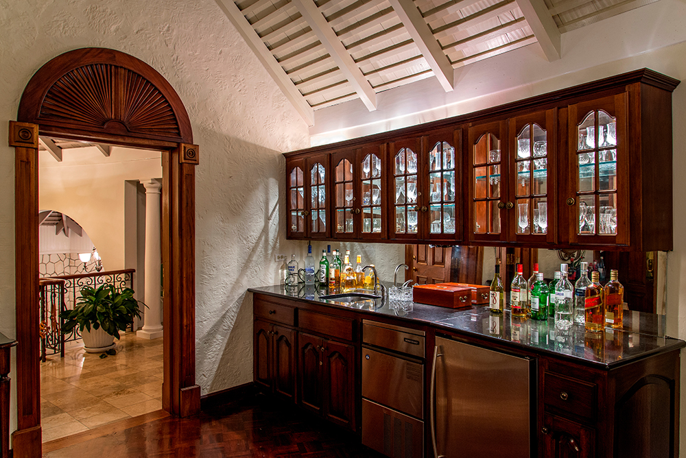 ... a gleaming glass and granite bar with fridge and ice maker.