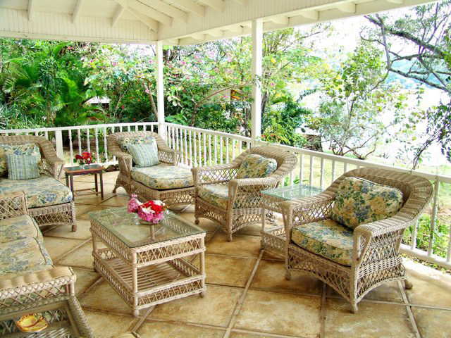 The living room opens wide to the 60' verandah ... furnished in wicker chaises, draped with flowering vines and overlooking the turquoise bay.