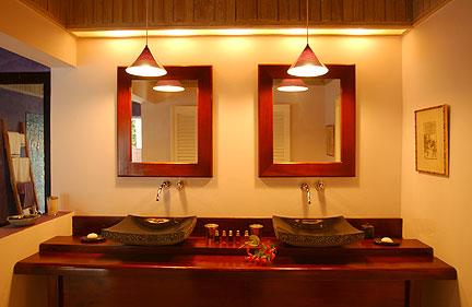 En-suite bathroom features designer granite sinks, stone bathtub ...