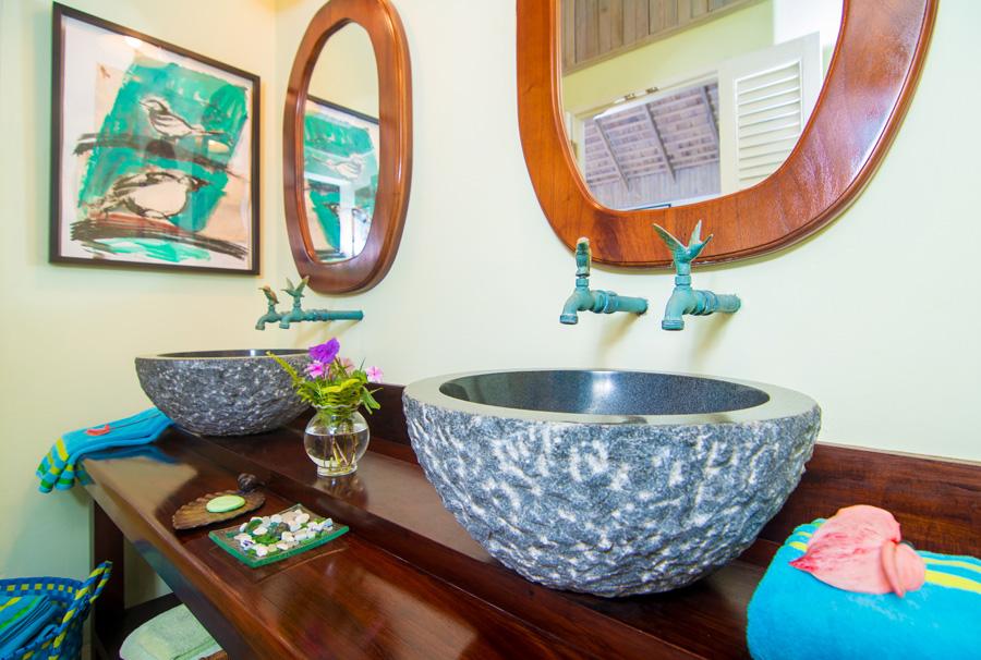 En-suite bathroom features designer granite sinks and oversize indoor shower room.