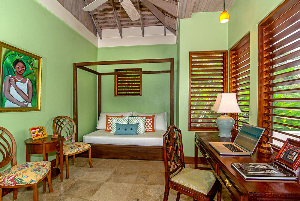 Adjoining the bedroom is a private study with twin daybed and mahogany desk.  Wide wraparound louvers reveal the lush west garden.