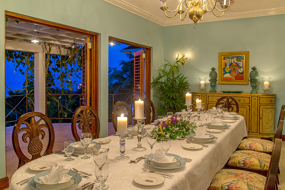 The formal dining room has custom-designed  pineapple chairs.  Wide doors open to the balcony and al fresco second dining area.